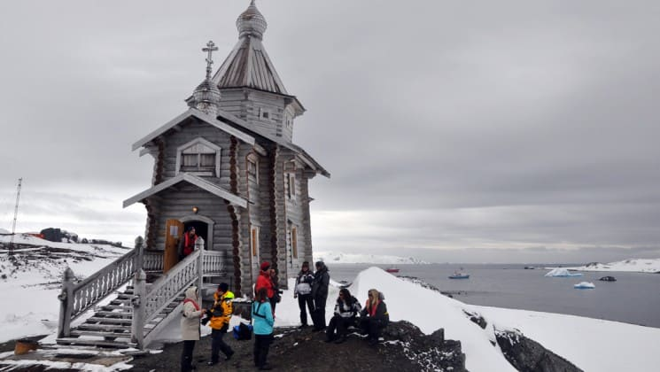 Passengers from the antarctic air cruise stand in front of a church on a bluff overlooking the ocean.