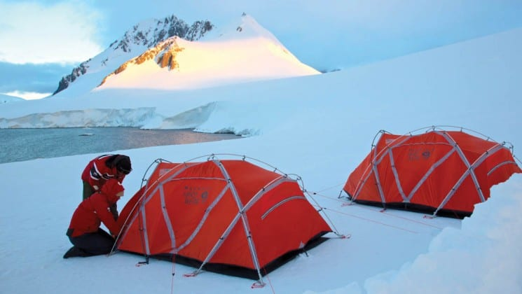 A person stands outside two tents set up on a snowy field in antarctica