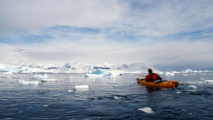 A kayak paddles through icebergs in Antarctica, on an excursion with the spirit of shackleton adventure cruise