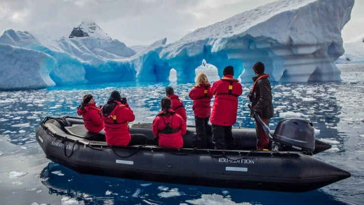 Guests from the spirit of shackleton expedition cruise sit in a zodiac with icebergs in the distance, at antarctica