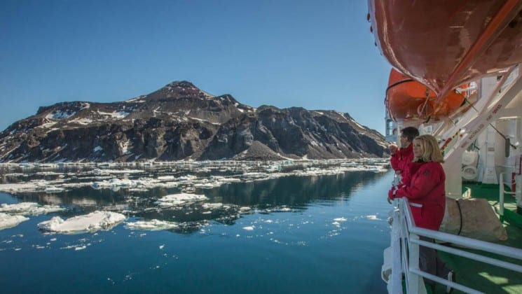 passengers aboard the Expedition ship for the quest to the antarctic circle look at icebergs and mountains reflecting in the calm water