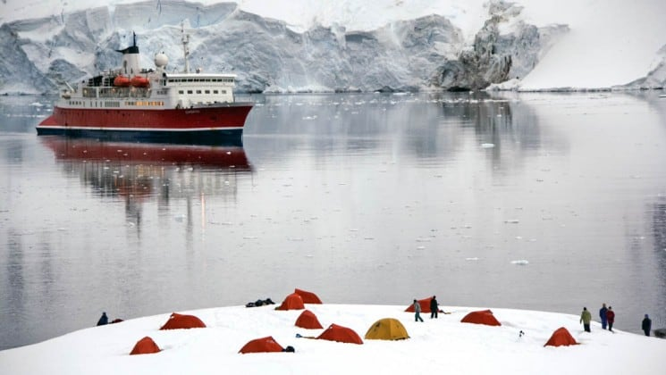 the spirit of shackleton expedition cruise ship is anchored in calm seas while tents are set up in the snow in the foreground in antarctica