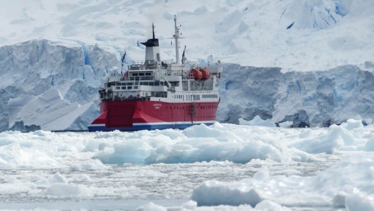A view over sea ice toward the ship that carries passengers on the quest to the antarctic circle