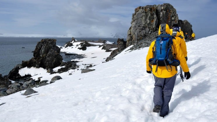 A person hikes on snow on a hill above the ocean in antarctica