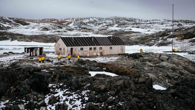 People stand outside a white building with a grey roof set on an antarctic landscape