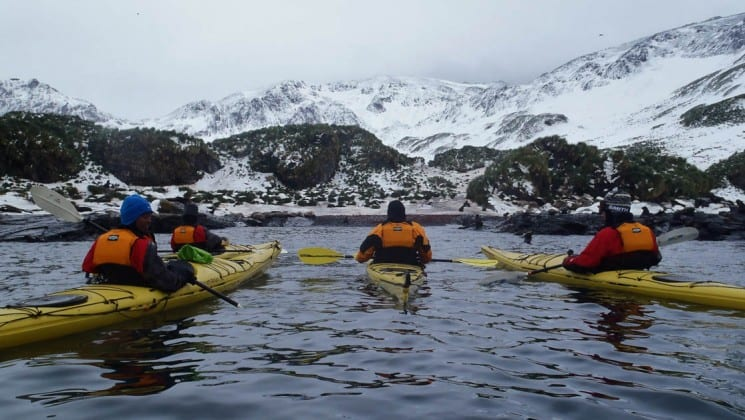 A group of kayakers paddle across a calm bay toward snowy mountains, as part of the crossing the antarctic circle cruise