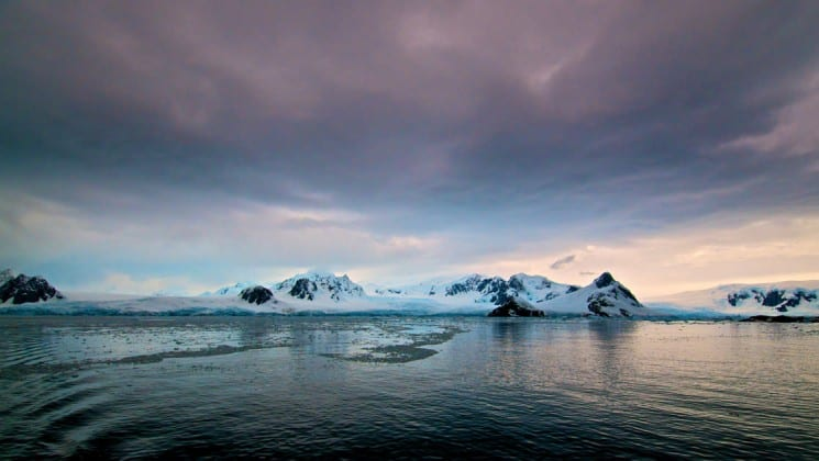 A landscape photo with snow mountains under a purple-blue sky at dusk in antarctica