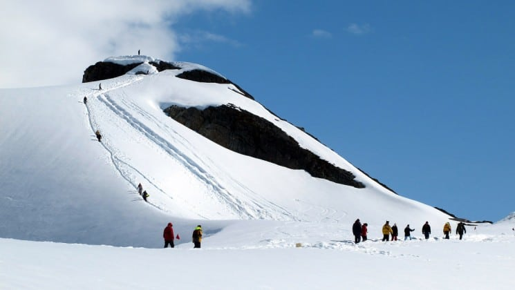 Passengers from the Polar Circle Air Cruise take a day's expedition to hike and explore the snowy mountains of antarctica