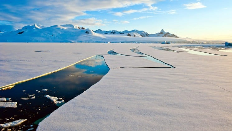 A trail is cut through ice sheets in antarctica, showing the path of the national geographic voyage ship through antarctica, with snow-capped mountains in the background