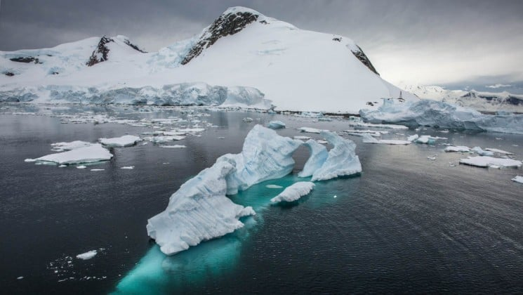 The tip of an iceberg rises from the ocean, as seen from the crossing the antarctic circle cruise ship