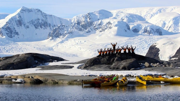 On a day's expedition, a group of people pose on land with sea kayaks in front in antarctica