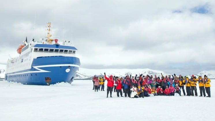 Passengers stand outside on the ice in front of a large ship that's part of the antarctica air cruise expeditions