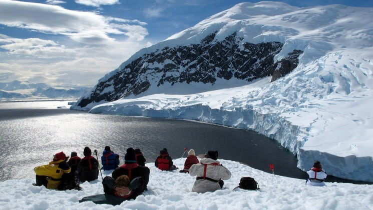 Guests from the Polar Circle Air Cruise sit on a snowy outlook, with a view of the ocean and icebergs in the distance, in antarctica