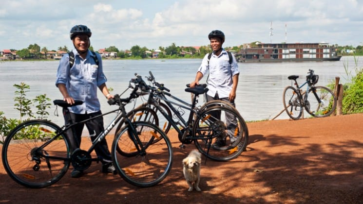 Two people stand next to bicycles along the Mekong River in Cambodia
