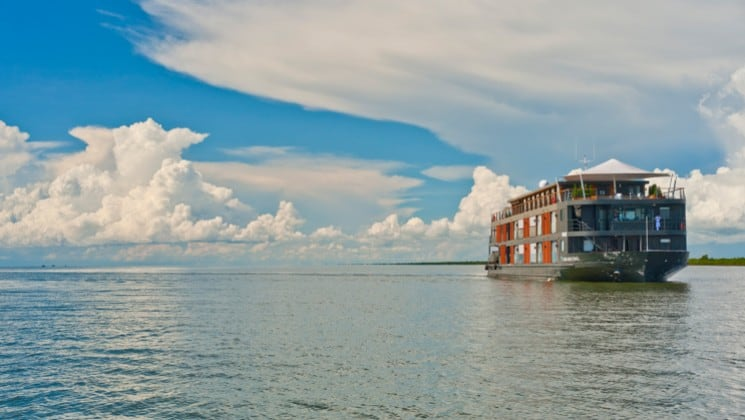 A river boat motors down the Mekong in Cambodia under a blue sky with white clouds