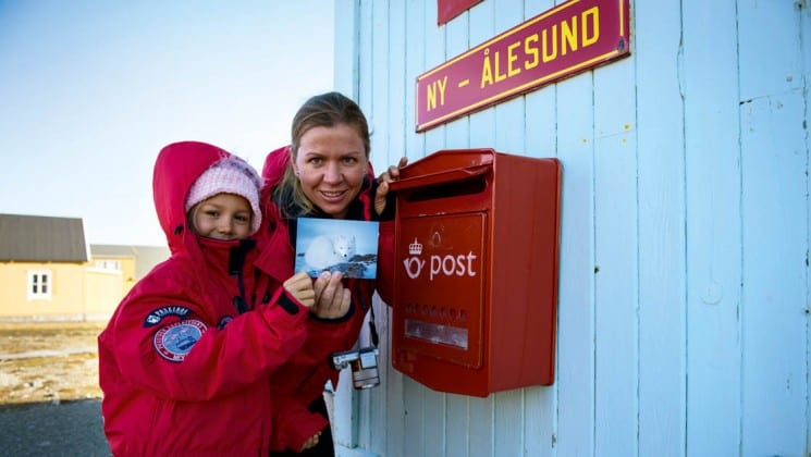 two people hold up a postcard to drop in the mail box in spitsbergen in the arctic circle
