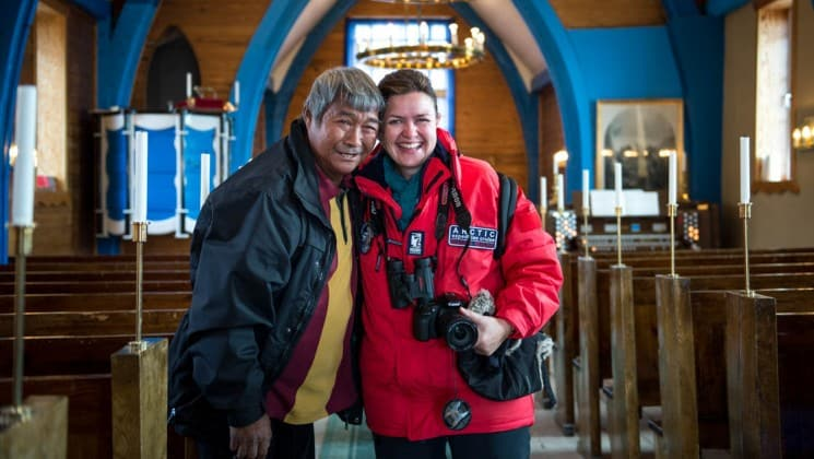two people pose for a photograph in a icelandic village in the arctic circle