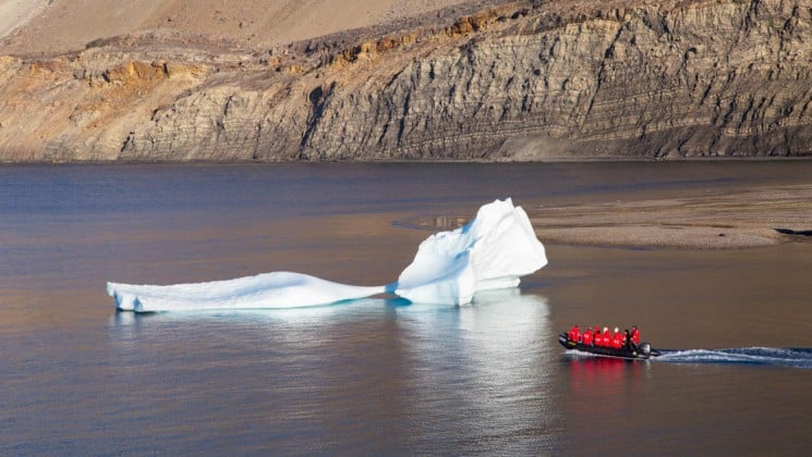 a zodiac boat motors past an iceberg near land in the arctic circle