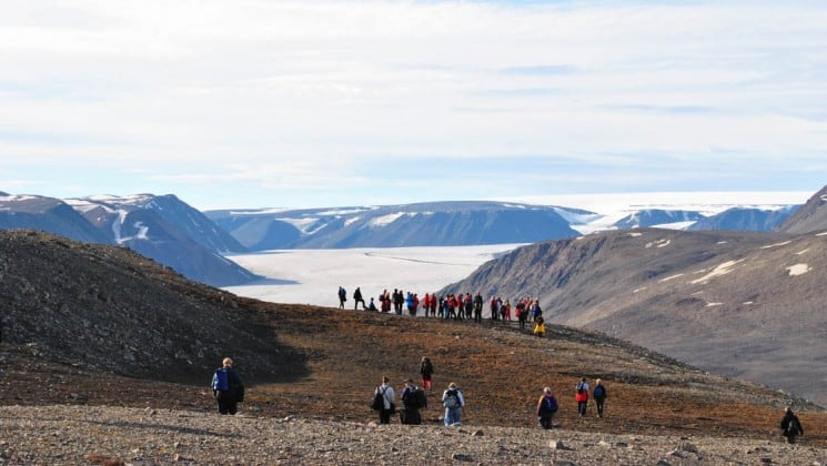 a group of people from the around spitsbergen expedition cruise take a hike on the tundra in the arctic circle with the ocean and mountains in the background