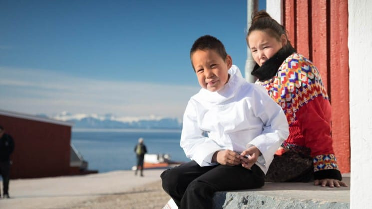 two people sit on a bench overlooking the ocean and snow-capped mountains in greenland