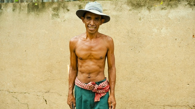 A shirtless man wears traditional clothing and poses for a portrait in Cambodia