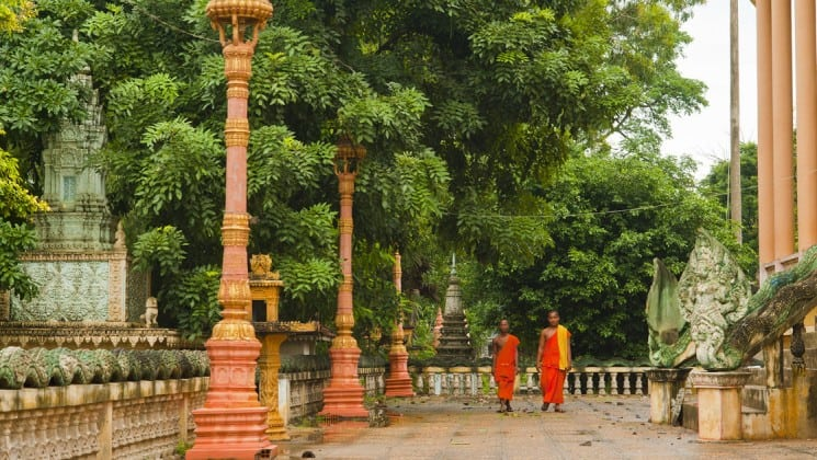 Two monks walk through a temple courtyard next to the jungle in cambodia