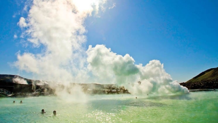 steam rises from a blue lagoon and geothermal hot springs in iceland