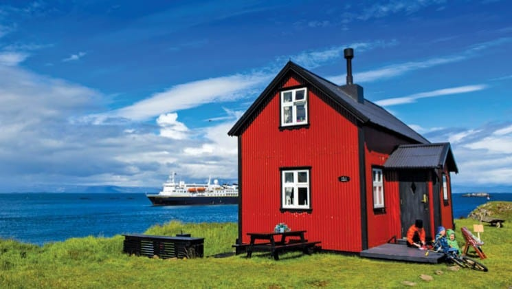 a bright red house on a green pasture in iceland while the national geographic explorer ship motors on the sea in the background