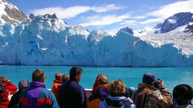 A group of passengers on the classic antarctica expedition cruise take in the view of the ocean and snow-capped mountains