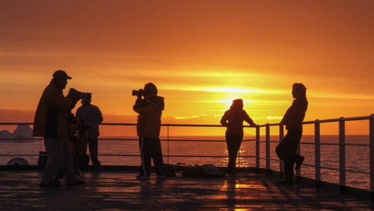 Passengers from the expedition cruise classic antarctica look over the railing of the ship while the sun sets in the background