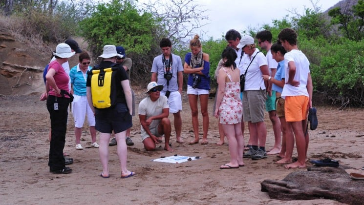 Passengers of the Coral small ship cruises listen to a guide give a lecture about flora, fauna, and wildlife on the Galapagos Islands