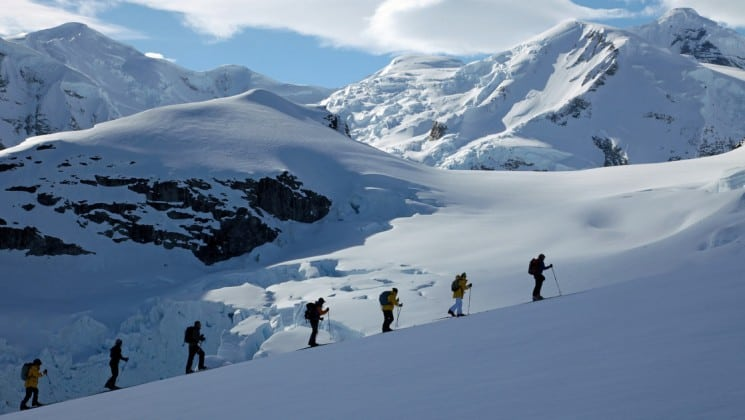 A group of passengers on the experience antarctica climb a snowy slope on snow shoes