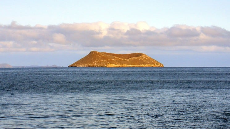 a volcanic, circular island named daphne sits on the horizon between the ocean and the sky at the galapagos