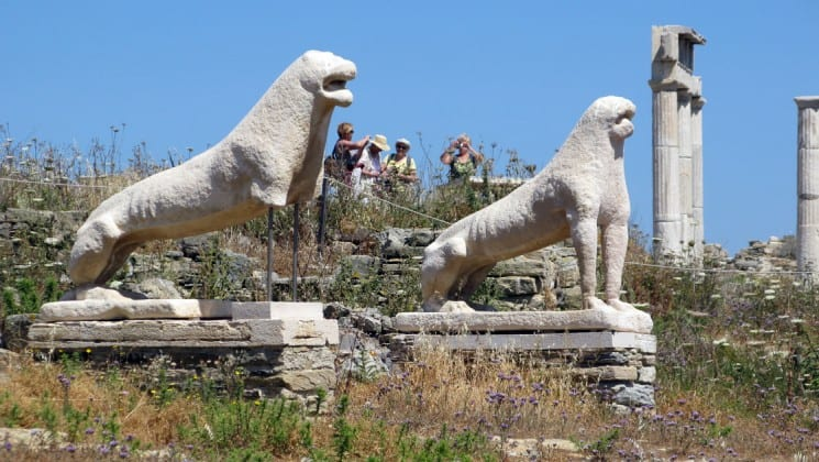 Ancient greek statues of lions stand above bushes in delos, greece