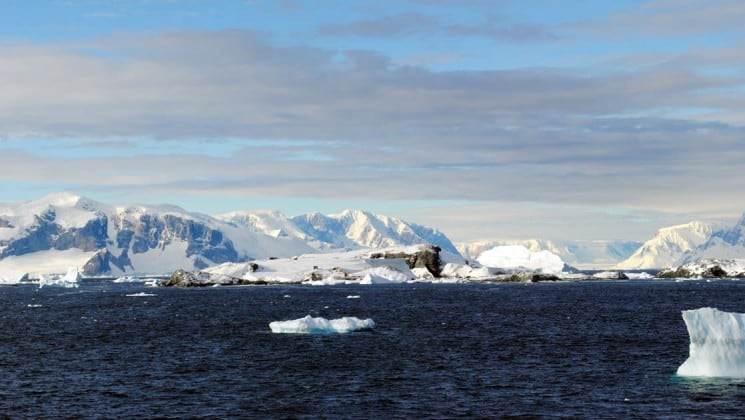 icebergs and snow mountains in the distance, with the ocean in the foreground, as seen from the polar circle cruise in antarctica