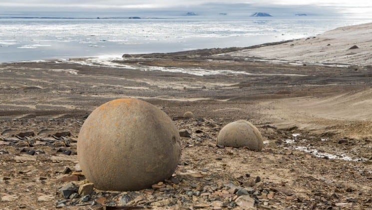 perfectly round rocks are nestled into the slope above the beach and the ocean in east greenland