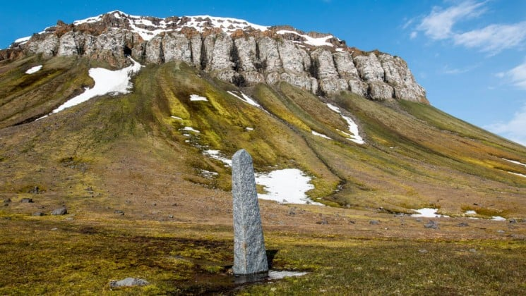 an upright stone monument is nestled in a green valley with rocky slabs and hillsides in east greenland