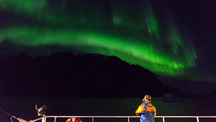 green northern lights cast a bright line on a dark sky, while a passenger aboard the arctic express ship looks on