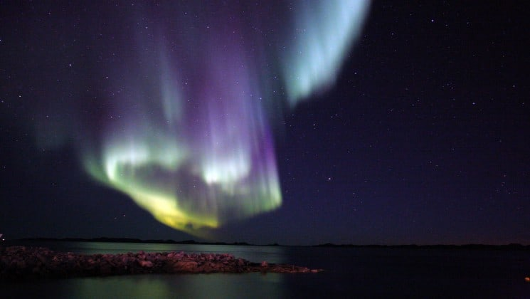 purple and yellow northern lights silhouette the mountains and the ocean in the arctic circle