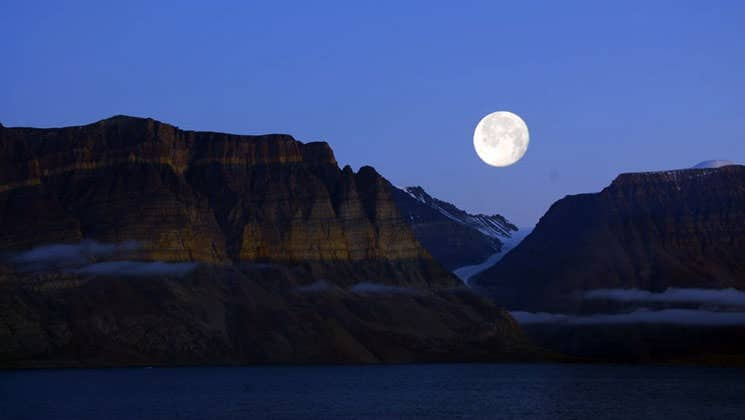 The moon rises above silhouetted mountains and the ocean in the arctic circle