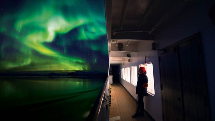 Green and blue northern lights illuminate the sky and the ocean just off the side of the ship for the arctic sights cruise