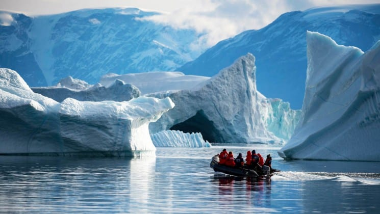 a zodiac boat motors toward icebergs in the arctic circle