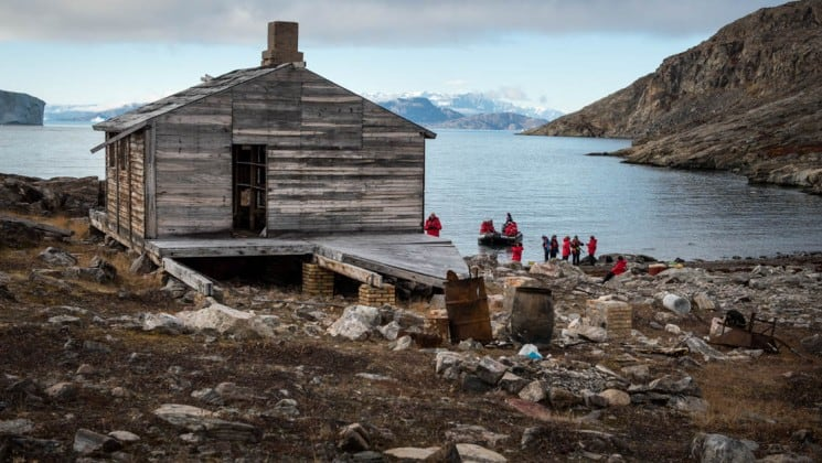 a wooden log cabin sits on a bluff overlooking the ocean and snow-capped peaks in the distance, as a stop in a inuit village for the arctic sights cruise