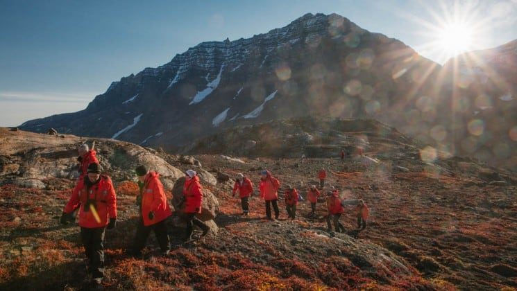 a group of people hike across the tundra in the arctic circle