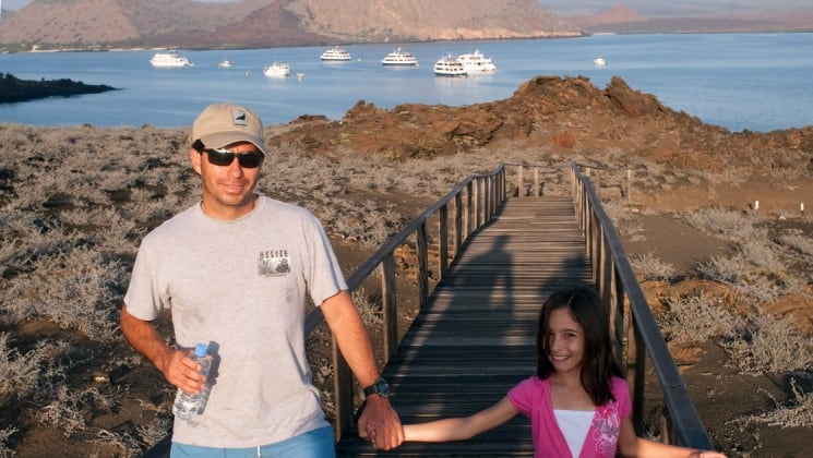a father and his daughter walk down a boardwalk with the ocean and yachts in the background
