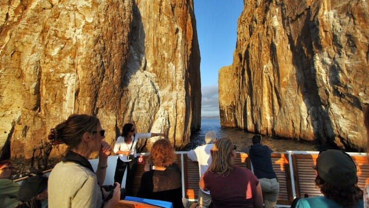 a group of passengers aboard the letty yacht look beyond the railing toward rock outcroppings and the ocean horizon at the galapagos islands