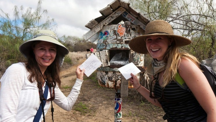 two women pose by the post office box at the galapagos islands