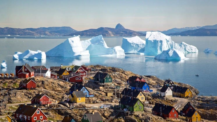 Colorful houses dot a rocky bluff overlooking the ocean, icebergs, and mountains, in the greenland, the arctic circle