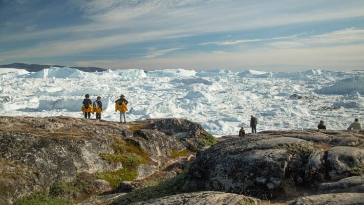 with icebergs in the distance, people hike on an expedition to explore greenland, the southern coasts, and disko bay in the arctic
