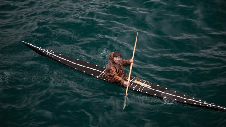 a man wearing a brown jacket paddles a traditional wooden kayak in greenland
